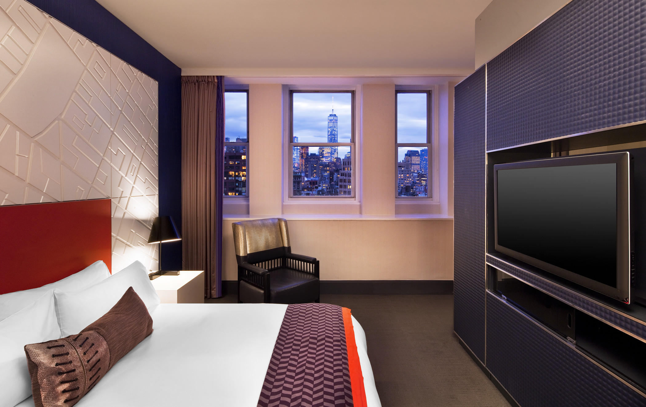 flat screen TV and bed with city view