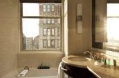 bathtub and sink below a clear glass window