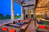 outdoor lounge on a balcony with cushioned couches at night