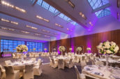white flower centerpieces on white dining tables in a large venue