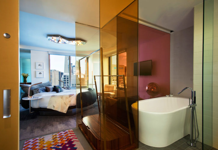 oval white bathtub with a doorway next to a large bed