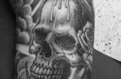 melting candle on top of skull tattoo