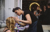 woman putting makeup on woman sitting