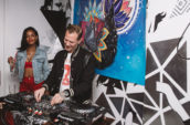 man standing and playing DJ mixer near woman smiling