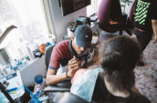 man sitting while tattooing woman on shoulder