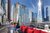 terrace with couch with red throw pillows overlooking city skyline