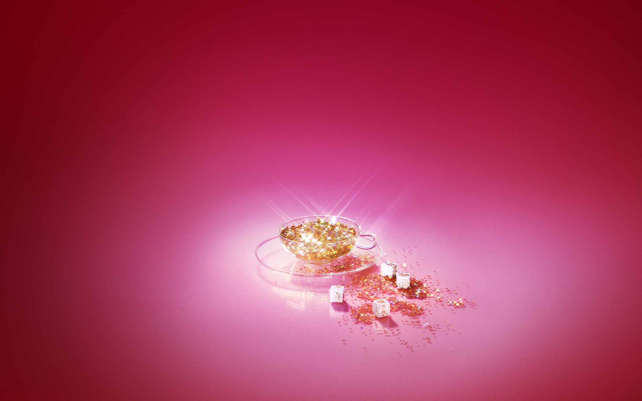 clear cup with gold sparkles on pink background