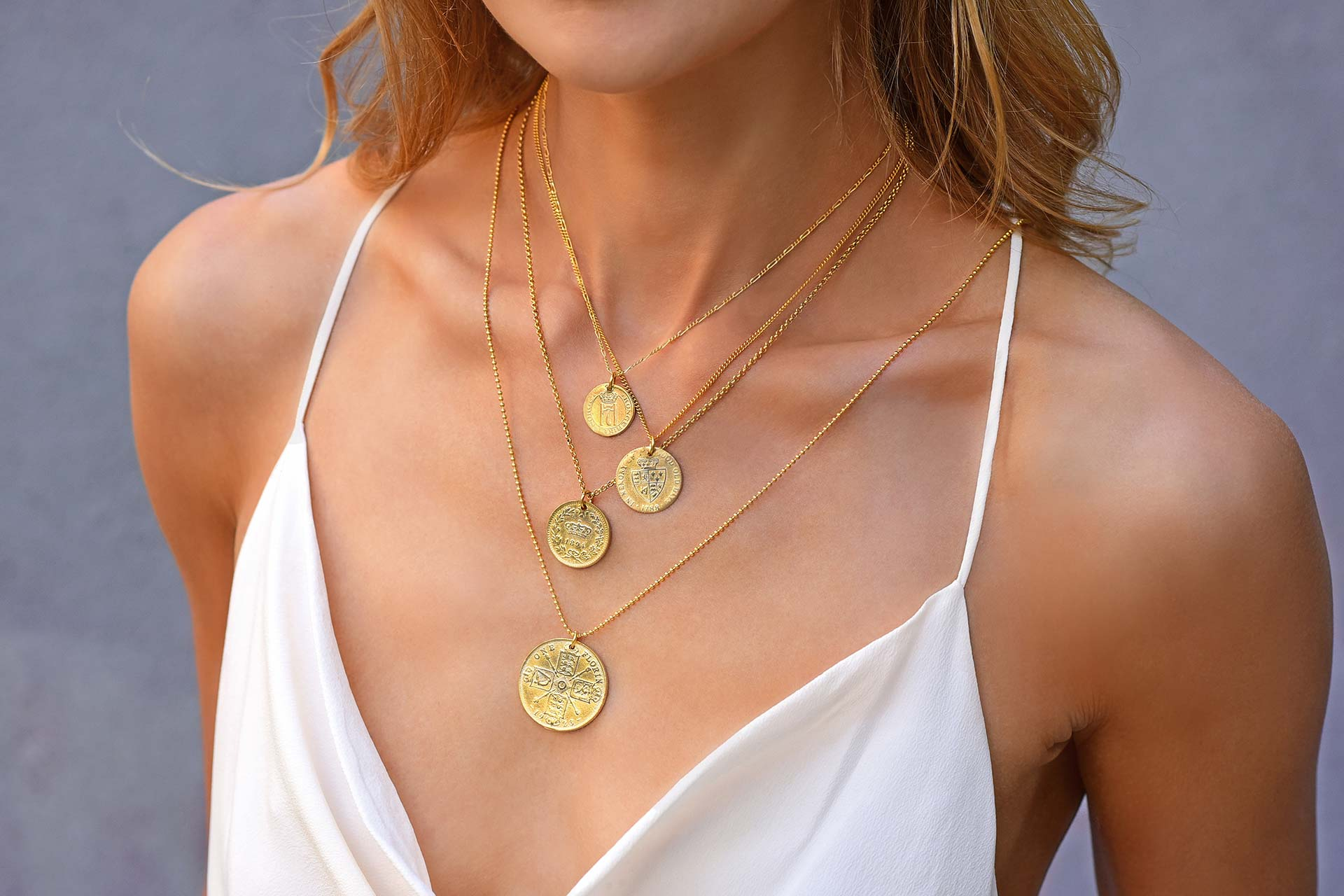 a woman wearing 4 golden charm necklaces