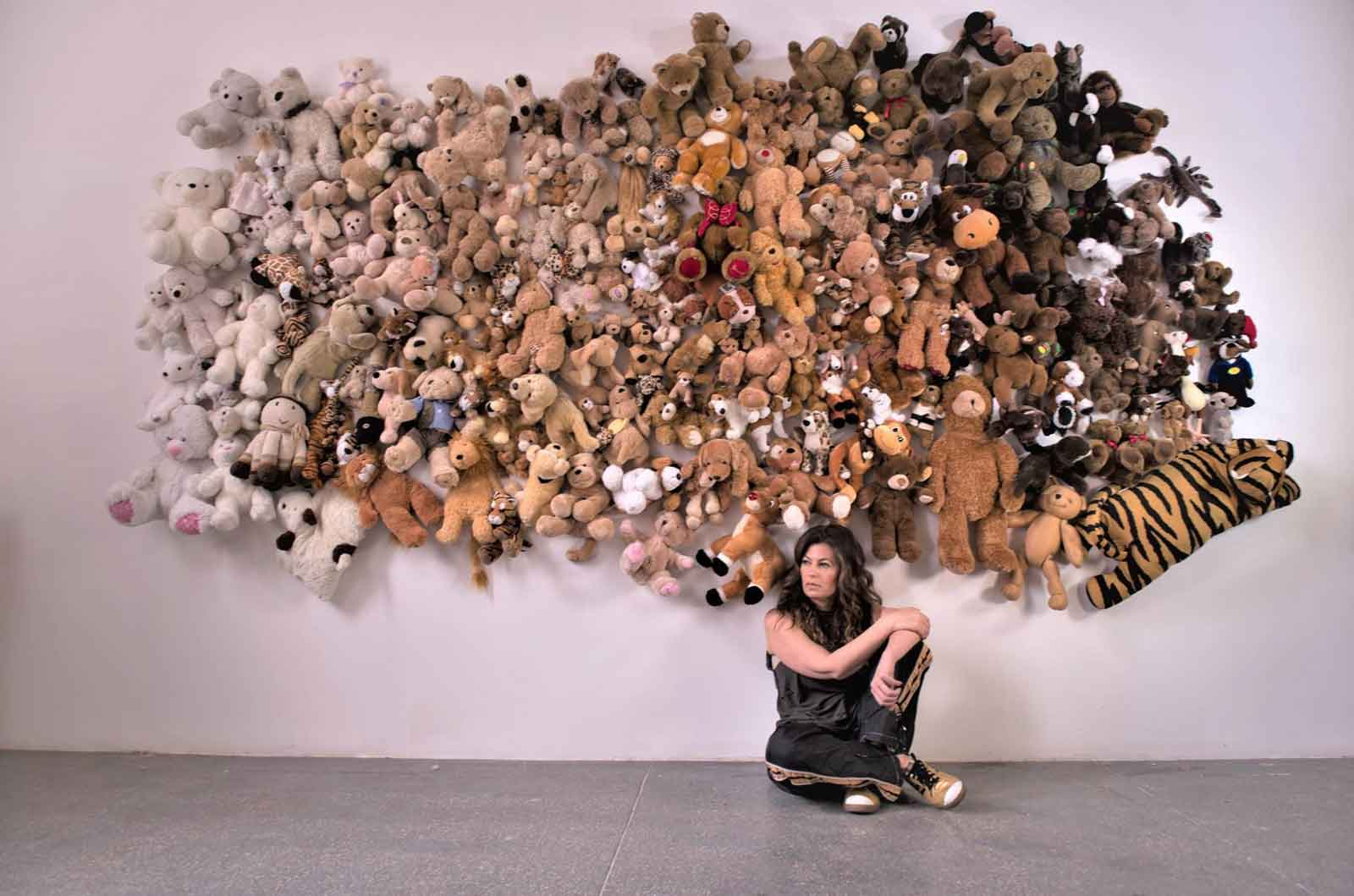 Ivy Nate in front of wall of stuffed animals