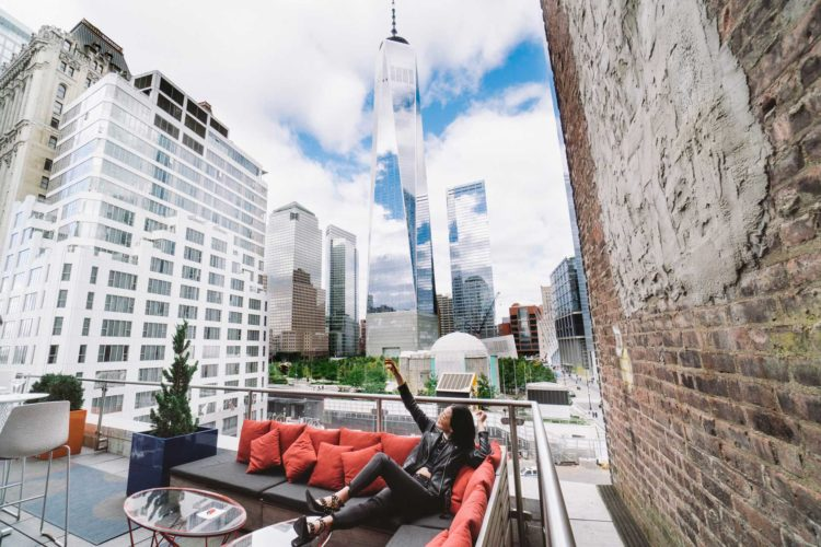 woman in leather jacket sitting down on outdoor patio in downtown new york