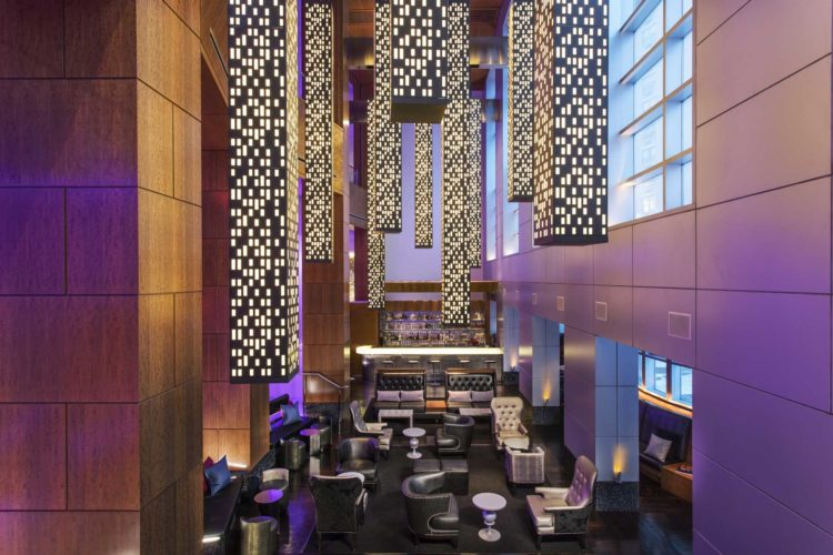 overhead view of modern luxury hotel bar with tall lighting fixtures hanging from ceiling