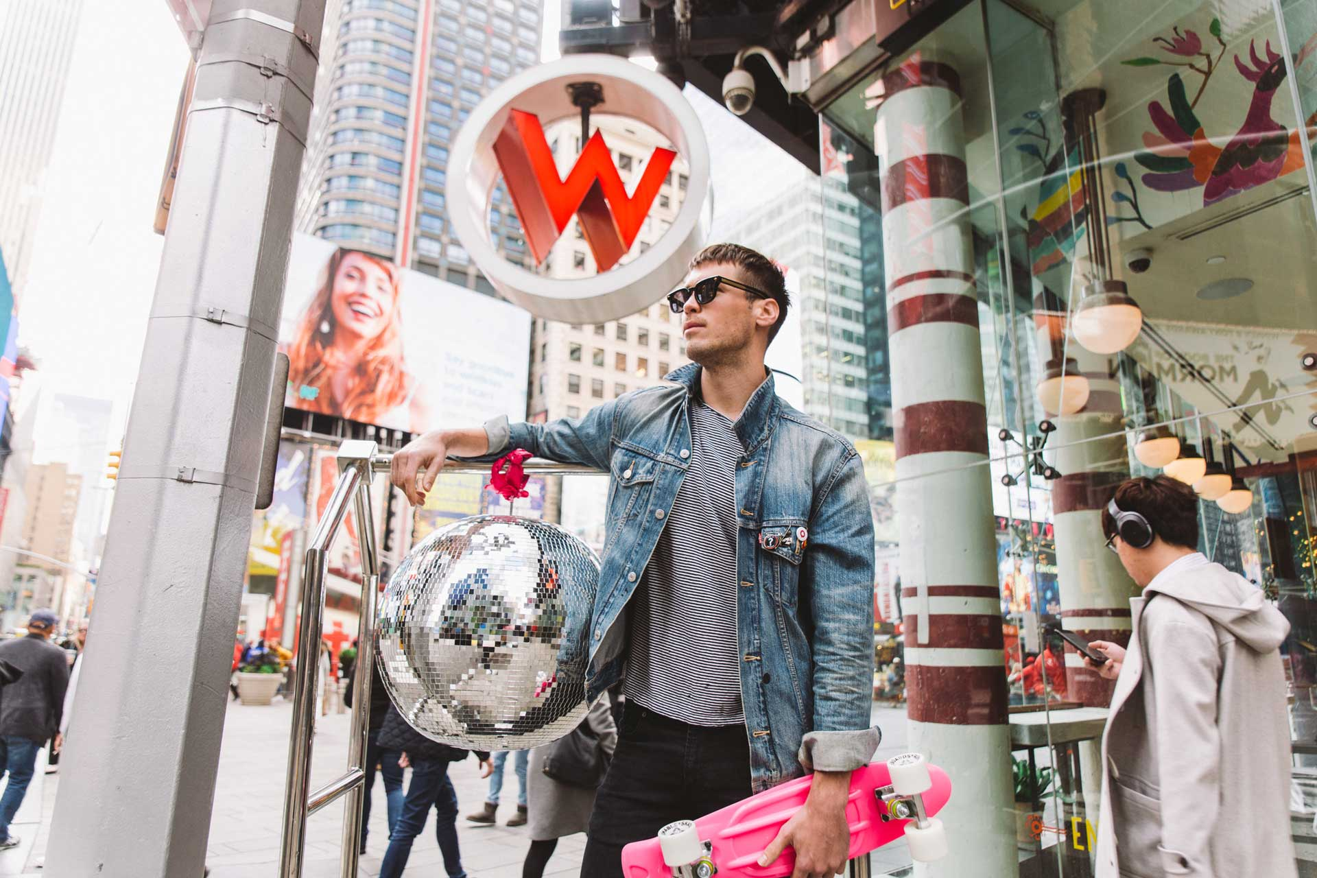 young man wearing sunglasses and denim jacket and holding pink skateboard outside of w hotel in new york